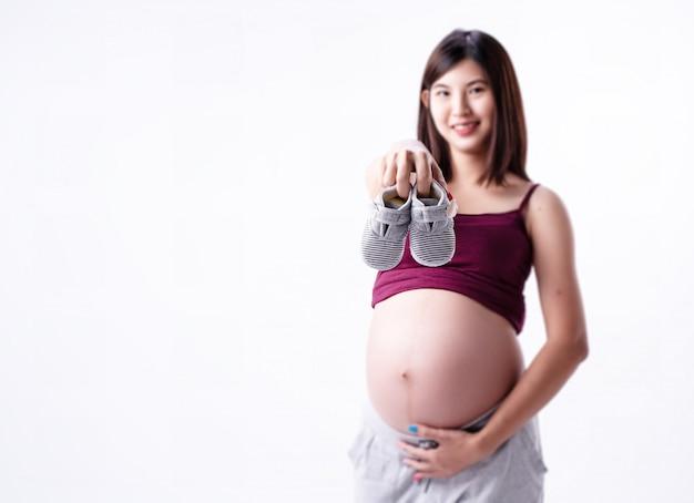 Nel fuoco selettivo delle scarpe da bambino stava tenendo dalla donna incinta blured Foto Premium