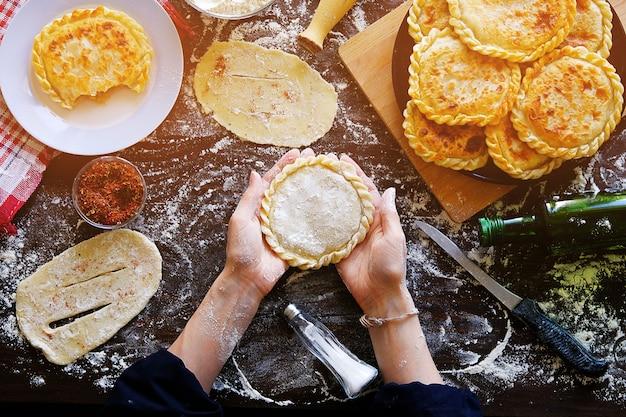 Nelle mani femminili del cuoco c'è una torta, una torta di pasta cruda Foto Premium