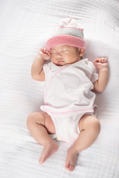Neonata adorabile felice che dorme in greppia. piccolo bambino che ha un pisolino nel letto dei genitori Foto Premium