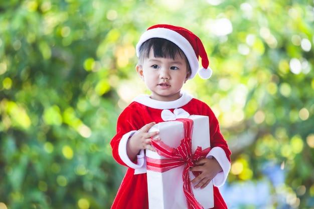 Neonata asiatica sveglia che indossa il vestito di santa che tiene il bello contenitore di regalo a disposizione Foto Premium