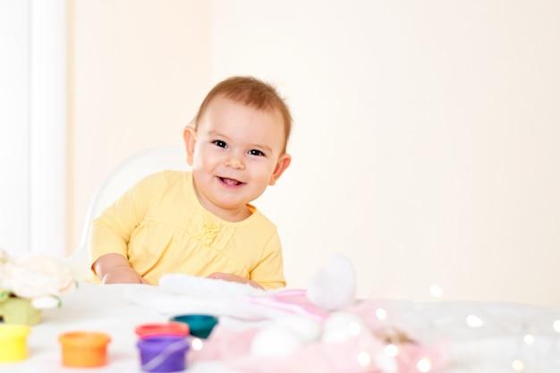 Neonata che si siede alla tavola e che dipinge infanzia felice sorridente delle uova di pasqua di festa Foto Premium