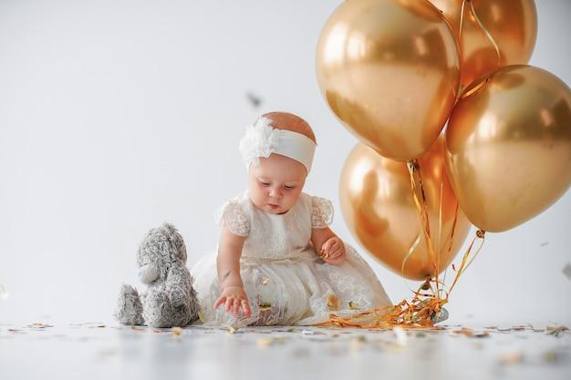 Neonata che si siede con un mazzo di palloni dorati Foto Premium