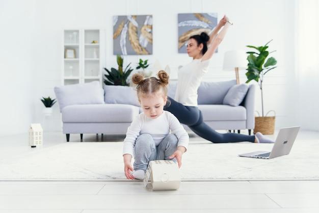 Neonata divertente che gioca a casa mentre la sua mamma sportiva che fa forma fisica e yoga si esercita sui precedenti. Foto Premium