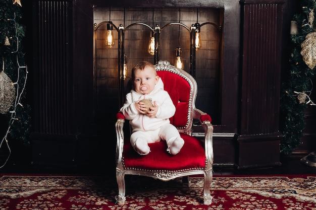 Neonata sorridente sotto l'albero di natale di decorazione di 1 anno nella sala. guardando la fotocamera. celebrazione. stagione delle vacanze. Foto Premium