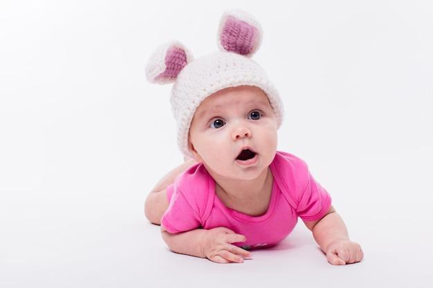 Neonata sveglia che si trova in una maglietta e un cappello rosa luminosi con le orecchie di coniglio Foto Premium
