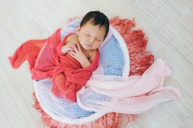 Neonato avvolto in una coperta che dorme in un cestino. concetto di infanzia, assistenza sanitaria, fecondazione in vitro Foto Premium