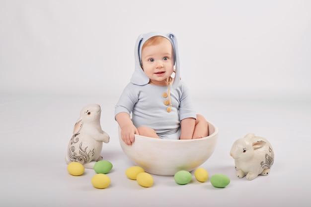 Neonato divertente sveglio con le orecchie del coniglietto e le uova di pasqua e i conigli variopinte. pasqua bambino. saluto modello di carta di pasqua. Foto Premium