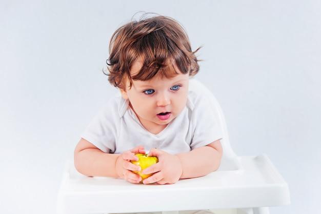 Neonato felice che si siede e che mangia Foto Gratuite