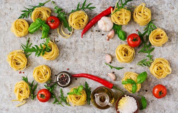 Nido di tagliatelle di pasta e ingredienti per cucinare (pomodori, aglio, basilico, peperoncino). vista dall'alto Foto Premium