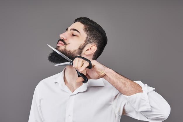 Niente più barba. ritratto del giovane bello che taglia la sua barba con le forbici e che esamina mentre stando contro il gray. nuova moda Foto Premium