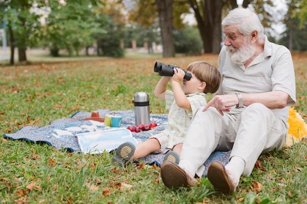 Nipote con il nonno guardando attraverso il binocolo Foto Gratuite