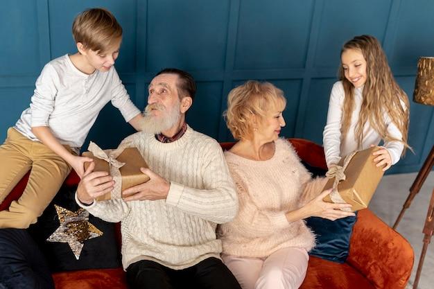 Nipoti di vista frontale che danno i regali ai nonni Foto Gratuite