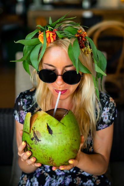 Noce di cocco bevente della bella donna nel caffè tropicale Foto Premium