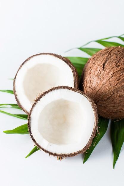 Noce di cocco con foglie verdi su sfondo bianco. Foto Premium