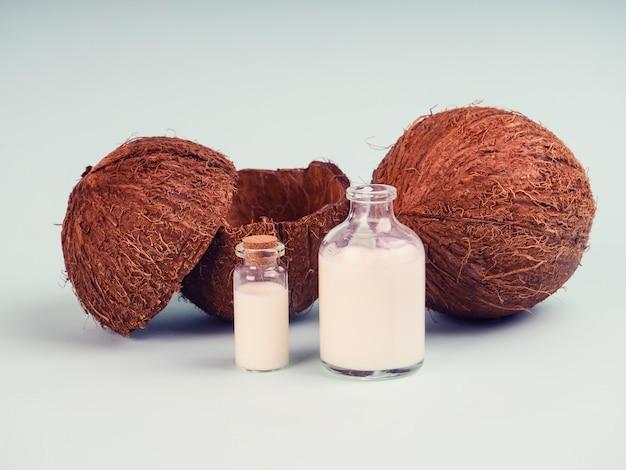 Noce di cocco e latte di cocco sulla tavola blu. olio di cocco con noci fresche. latte di cocco, olio di truciolo in provetta per ricerca, superfood, olio naturale, cosmetici Foto Premium