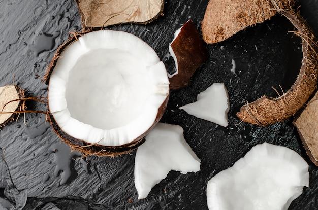 Noce di cocco rotta fresca mezza sul fondo nero dell'ardesia. Foto Premium