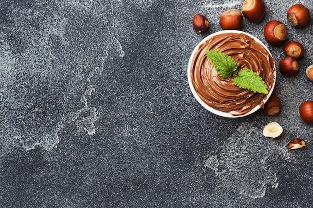 Noce di nocciole al cioccolato in un piatto su uno sfondo di cemento scuro con nocciole. concetto di colazione. copia spazio. Foto Premium