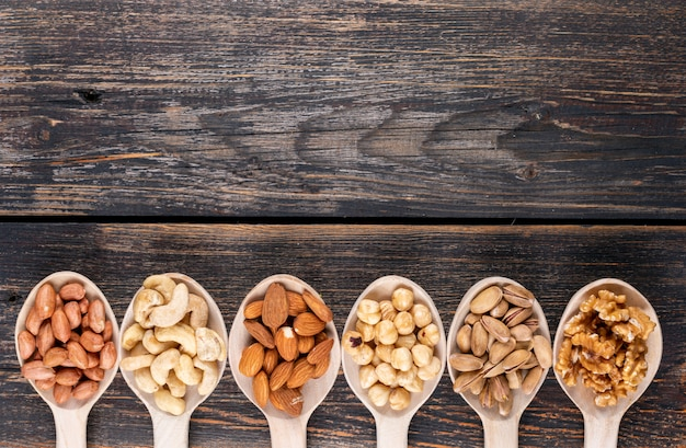 Noci assortiti e frutta secca in un cucchiaio di legno con noci pecan, pistacchi, mandorle, arachidi, anacardi, pinoli vista dall'alto Foto Gratuite