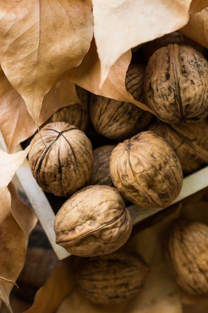 Noci intere in scatola di legno, foglie autunnali secche marroni. Foto Premium