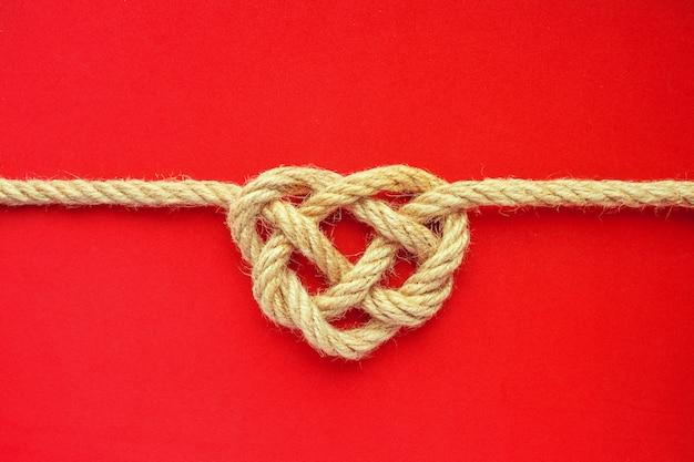 Nodo della corda di forma del cuore su fondo rosso. nodo celtico corda di iuta. concetto di amore Foto Premium