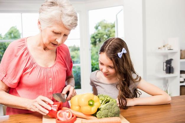 Nonna e nipote che affettano le verdure nella cucina Foto Premium
