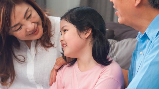 Nonni asiatici che parlano con la nipote a casa. il senior cinese, la vecchia generazione, il nonno e la nonna che utilizzano il tempo della famiglia si rilassano con il bambino della ragazza che si trova sul sofà nel concetto del salone. Foto Gratuite