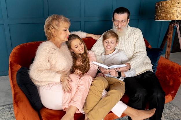 Nonni che leggono un libro con i loro nipoti Foto Gratuite