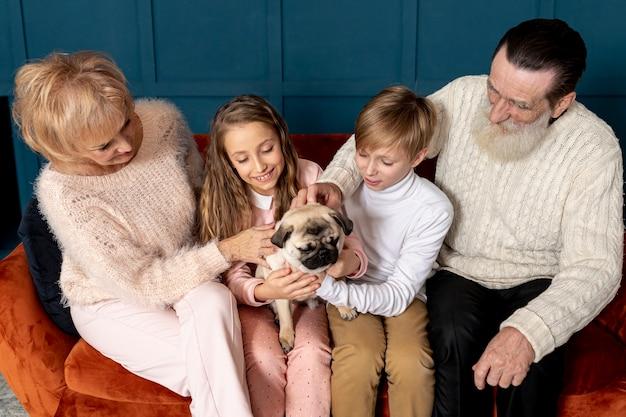 Nonni e nipoti che giocano con il cane Foto Gratuite