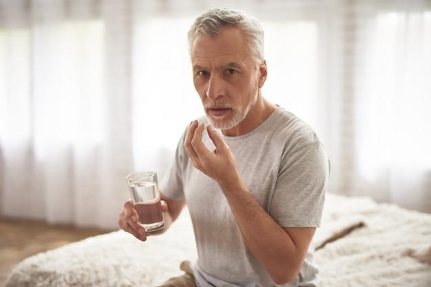 Nonno che prende le pillole nel dolore cronico di mattina. Foto Premium