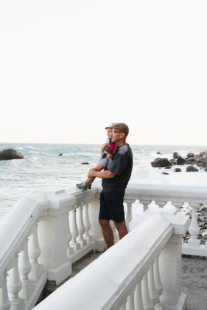 Nonno che tiene nipote e guardando il mare Foto Gratuite