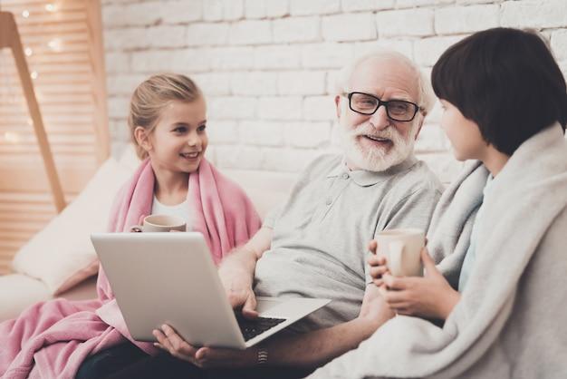 Nonno e bambini guarda film con tazze di tè. Foto Premium
