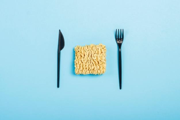 Noodles istantanei asiatici e piatti monouso in plastica su una superficie blu. il concetto di cibi pronti, fast food, cibo spazzatura. vista piana, vista dall'alto. Foto Premium