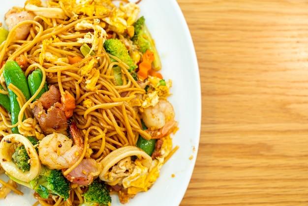 Noodles saltati in padella con frutti di mare e verdure Foto Premium