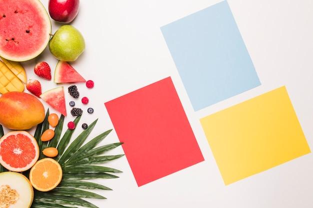 Nota appiccicosa gialla blu rossa e frutti diversi a foglia di palma Foto Gratuite