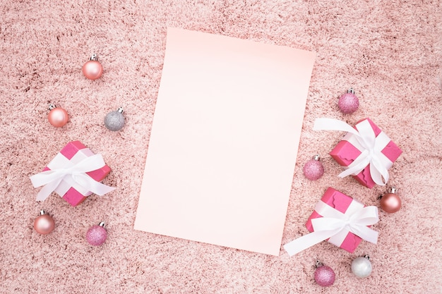 Nota di saluto con scatole regalo di natale e palline su un tappeto rosa con texture Foto Gratuite