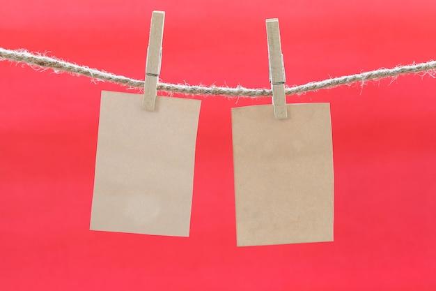 Nota marrone vuota su clothesline e sfondo rosso. Foto Premium