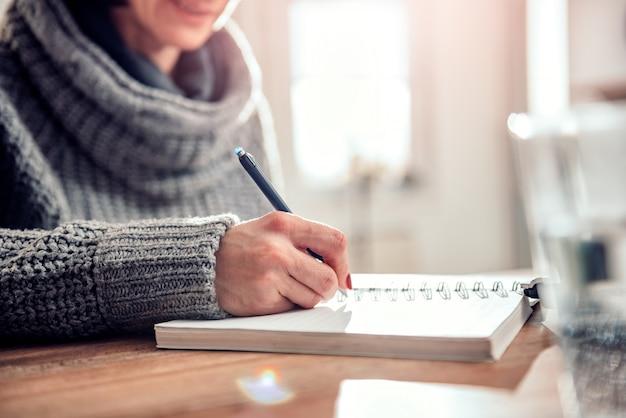 Note di scrittura della donna nel taccuino all'ufficio Foto Premium