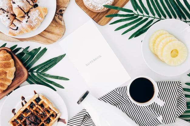 Notebook circondato da croissant; cialde; fette di ananas; bottiglia e tazza di caffè su sfondo bianco Foto Gratuite