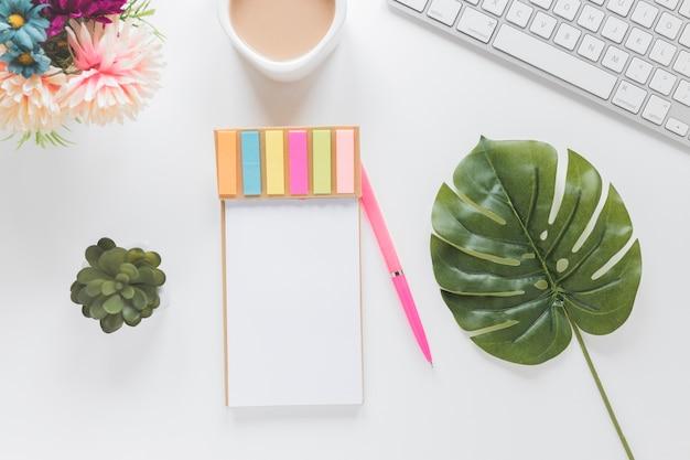 Notebook con adesivi vicino tazza di caffè, tastiera e piante Foto Gratuite