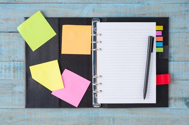 Notebook e penna su tavola di legno blu Foto Gratuite