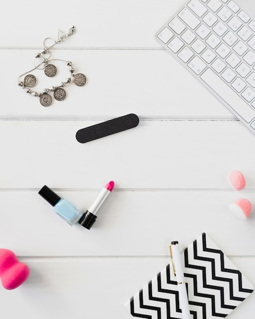 Notebook e prodotti di bellezza vicino alla tastiera Foto Gratuite