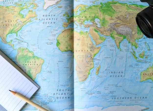 Notebook foderato con matita bianca e fotocamera sulla mappa del mondo Foto Premium