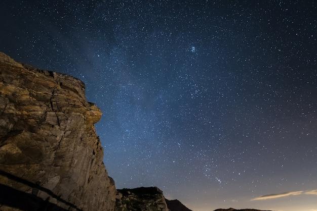 Notte sulle alpi sotto il cielo stellato e le maestose scogliere rocciose sulle alpi italiane Foto Premium