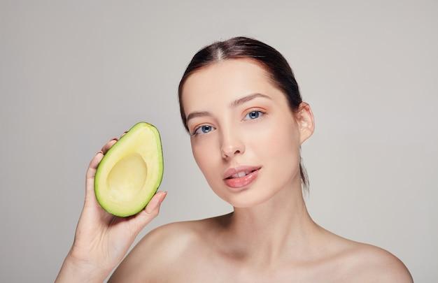 Nuda donna dalla pelle perfetta con avocado nella mano destra Foto Premium