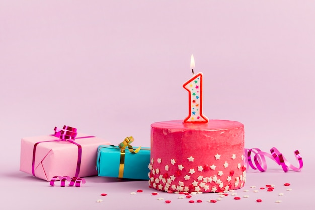 Numero una candela sulla torta rossa con granelli di stelle; scatole regalo e stelle filanti su sfondo rosa Foto Gratuite