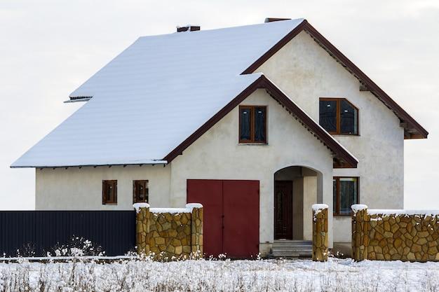 Nuova casa residenziale a due piani con recinzione in pietra di fronte Foto Premium
