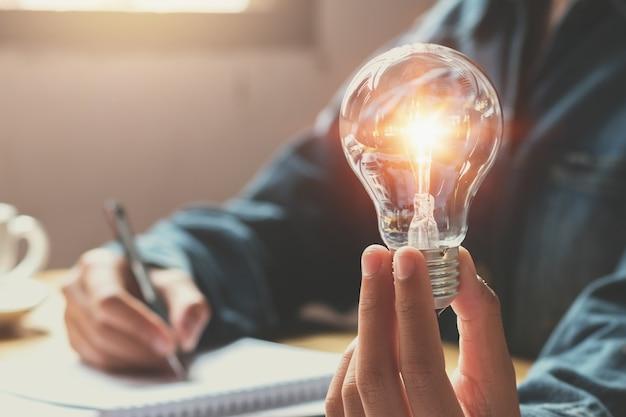 Nuova idea e concetto creativo per la mano della donna di affari che tiene lampadina Foto Premium
