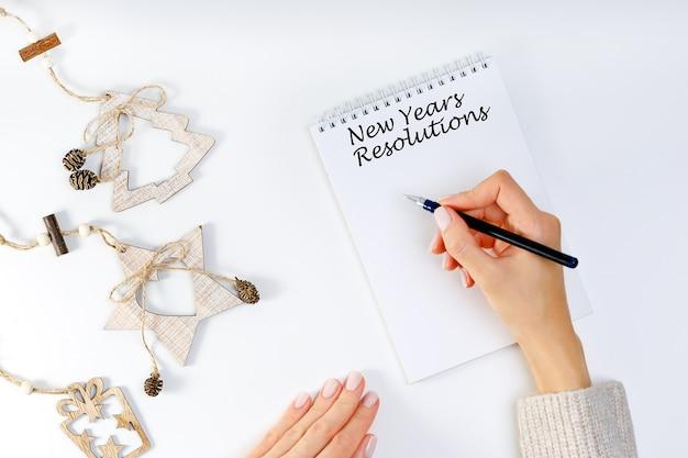 Nuovi anni di risoluzione con una persona in possesso di una penna e un quaderno. risoluzioni, obiettivi per il nuovo anno. Foto Premium