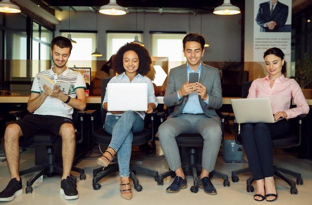 Nuovi candidati con i loro gadget in ufficio Foto Gratuite