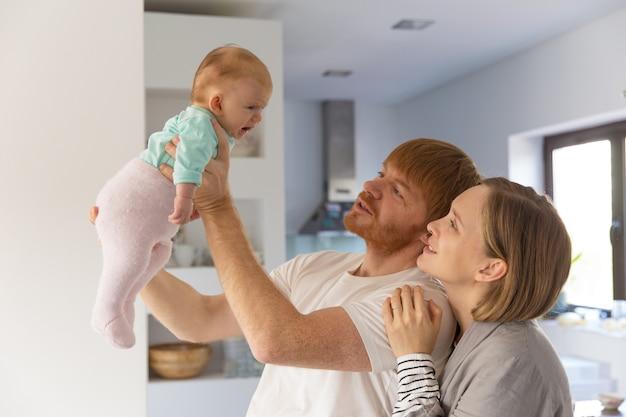Nuovi genitori felici che tengono e che esaminano bambino gridante Foto Gratuite